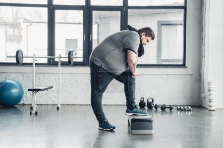 Photo for Overweight man with towel exercising on step platform at sports center - Royalty Free Image