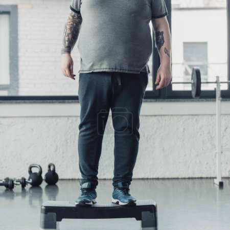 Photo for Cropped view of overweight tattooed man standing on step platform at sports center - Royalty Free Image