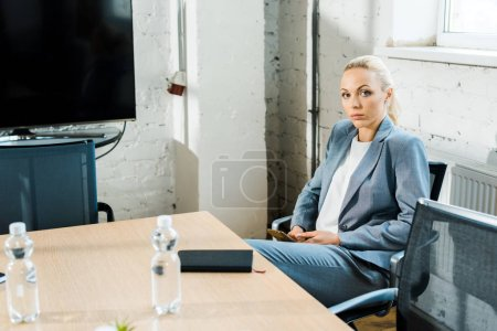 Photo for Attractive blonde business coach sitting in conference room and looking at camera - Royalty Free Image
