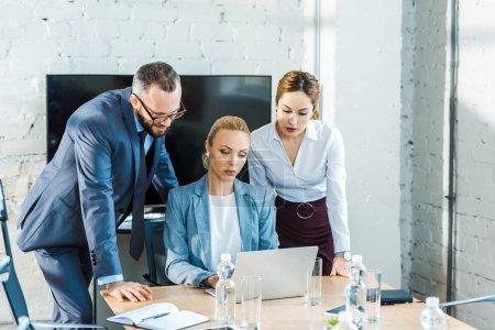 Photo pour Bel homme dans des glaces près des femmes d'affaires attirantes regardant l'ordinateur portatif - image libre de droit
