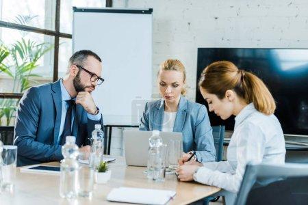 Photo pour Bel homme regardant l'ordinateur portatif tout en s'asseyant près des femmes d'affaires dans la salle de conférence - image libre de droit