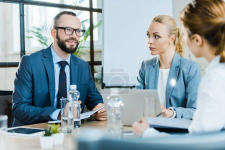 Photo for Cheerful businessman sitting with attractive businesswomen in conference room - Royalty Free Image