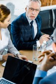 selective focus of businessman in eye glasses looking at coworker in modern conference room
