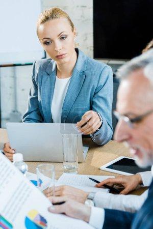 Photo pour Focus sélectif de femme d'affaires attrayante utilisant l'ordinateur portatif près du collègue - image libre de droit