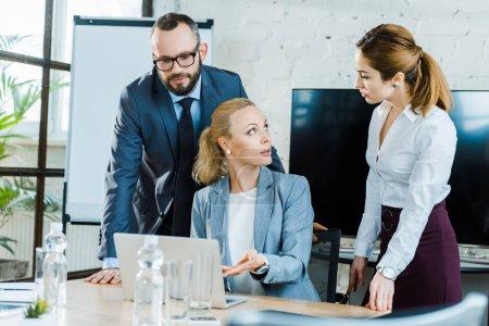 Photo pour Femme d'affaires attrayante faisant des gestes tout en s'asseyant près de l'ordinateur portatif et regardant le collègue - image libre de droit