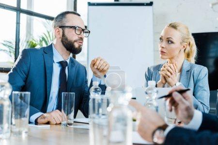 Photo pour Foyer sélectif de barbu homme d'affaires parler près de collègues dans la salle de conférence - image libre de droit