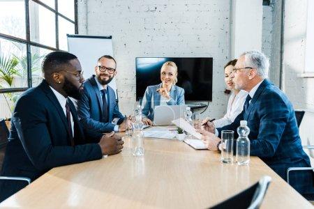Foto de Cheerful multicultural businessmen in eye glasses and attractive businesswomen sitting in conference room - Imagen libre de derechos