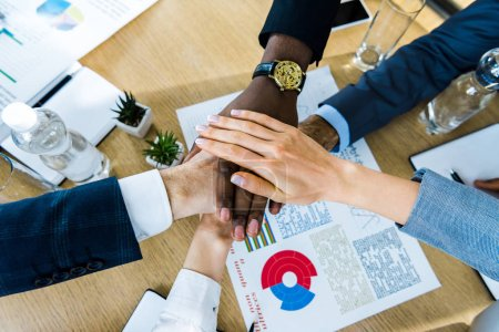 Foto de Top view of multicultural men and women putting hands together near charts and graphs - Imagen libre de derechos