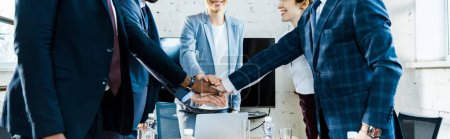 Photo pour Plan panoramique de femmes d'affaires gaies et d'hommes multiculturels mettant la main ensemble - image libre de droit