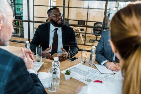 Photo pour Foyer sélectif de l'homme américain africain gai dans des lunettes s'asseyant dans la salle de conférence avec des collègues - image libre de droit