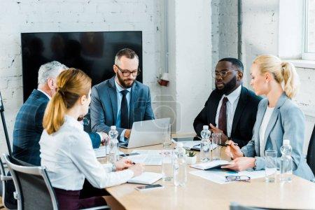 Photo pour Hommes d'affaires multiculturels ayant la conversation avec des femmes d'affaires dans la salle de conférence - image libre de droit