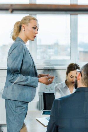 Photo pour Focus sélectif de l'entraîneur d'affaires blonde attrayante restant près de collègues dans la salle de conférence - image libre de droit