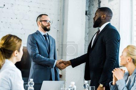Photo pour Hommes d'affaires multiculturels serrant la main près de collègues au bureau - image libre de droit