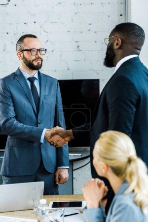 Foto de Multicultural businessmen shaking hands near blonde coworker in office - Imagen libre de derechos