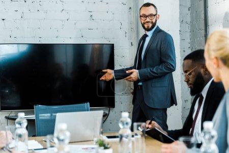 Photo pour Coach d'affaires gai dans des lunettes faisant des gestes près de la télévision avec écran blanc et collègues multiculturels - image libre de droit