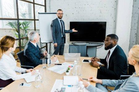 Photo pour Entraîneur d'affaires dans l'usure formelle gesticulant près de la télévision avec écran blanc et collègues multiculturels - image libre de droit
