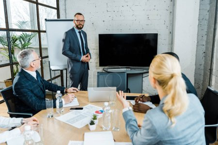 Photo for Business coach in formal wear standing near tv with blank screen and multicultural coworkers - Royalty Free Image