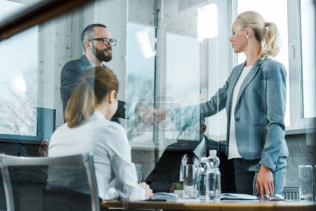 Photo for Handsome bearded  business coach shaking hands with blonde woman near multicultural coworkers - Royalty Free Image