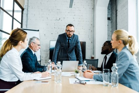 Photo for Handsome business coach standing near multicultural businessmen and businesswomen - Royalty Free Image