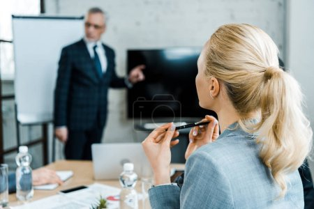 Photo for Selective focus of blonde businesswoman holding pen while looking at business coach - Royalty Free Image