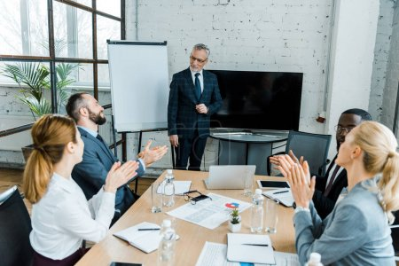 Photo for Selective focus of business coach standing near white board near multicultural coworkers clapping hands in conference room - Royalty Free Image