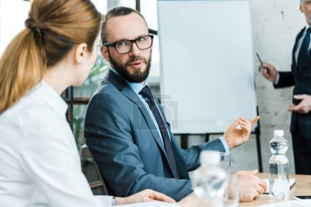 Photo pour Selective focus of bearded man talking with woman near business coach in conference room - image libre de droit