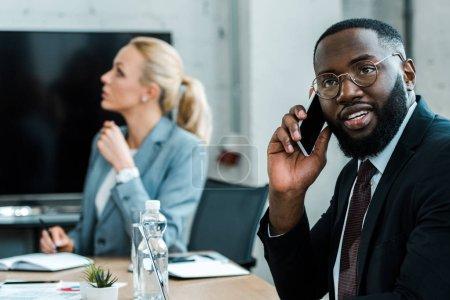 Photo pour Foyer sélectif de l'homme afro-américain parlant sur smartphone près de collègue blonde - image libre de droit