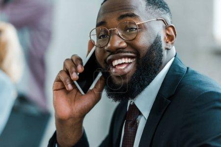 Photo pour Homme afro-américain barbu et heureux parlant sur smartphone - image libre de droit