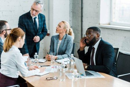 Photo pour Foyer sélectif de l'homme américain africain parlant sur le smartphone près de l'ordinateur portable et des collègues - image libre de droit