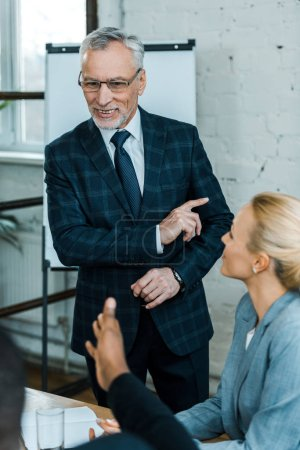 Photo for Selective focus of cheerful business coach in glasses pointing with finger near multicultural coworkers - Royalty Free Image