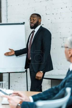 Photo for Selective focus of handsome african american business coach talking and gesturing near white board - Royalty Free Image