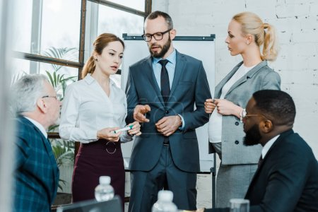 Photo pour Selective focus of businessman talking and pointing with finger near multicultural coworkers and pregnant blonde woman - image libre de droit
