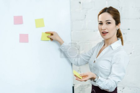 Photo for Attractive business coach putting sticky notes on white board - Royalty Free Image
