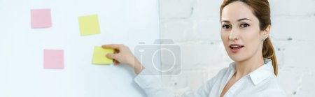 Photo for Panoramic shot of attractive business coach putting sticky notes on white board - Royalty Free Image