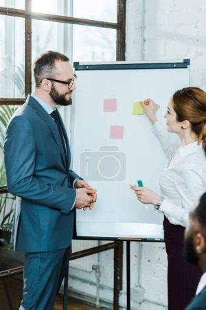 Photo pour Foyer sélectif de l'homme d'affaires regardant la femme d'affaires restant près du tableau blanc avec des notes collantes - image libre de droit