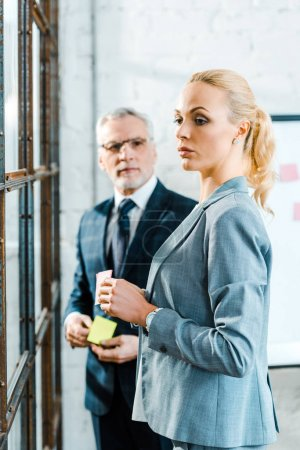 Photo for Selective focus of attractive blonde woman holding sticky note near businessman - Royalty Free Image