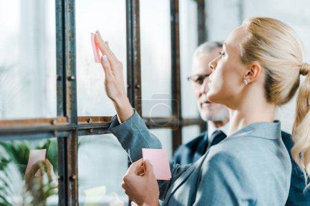 Photo pour Foyer sélectif de femme blonde attrayante mettant note collante sur la fenêtre près de l'homme d'affaires - image libre de droit