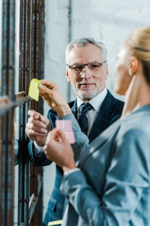 Photo pour Foyer sélectif de l'homme d'affaires dans les lunettes de vue regardant femme blonde tenant des notes collantes près de la fenêtre - image libre de droit