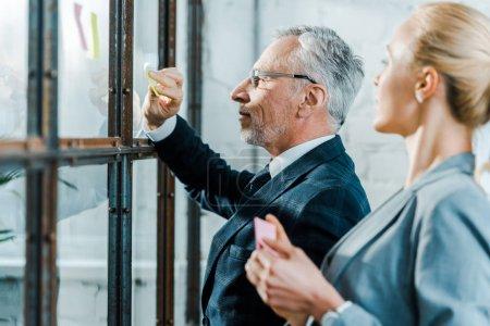 Photo pour Foyer sélectif de l'homme d'affaires dans les lunettes de mettre des notes collantes sur la fenêtre près de la femme d'affaires - image libre de droit