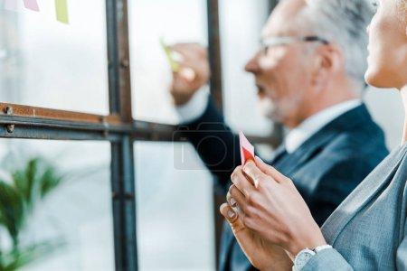 Foto de Enfoque selectivo de la mujer de negocios mirando a hombre de negocios poniendo nota adhesiva en la ventana - Imagen libre de derechos