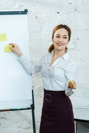 Photo for Cheerful business coach putting sticky notes on white board - Royalty Free Image