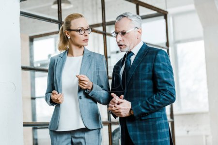 Photo for Bearded businessman talking with attractive blonde businesswoman - Royalty Free Image