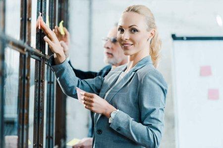 Photo pour Foyer sélectif de femme d'affaires blonde gaie mettant note collante sur la fenêtre près de l'homme d'affaires - image libre de droit