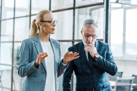 Photo pour Attrayant blonde femme d'affaires geste tout en parlant avec barbu homme d'affaires - image libre de droit