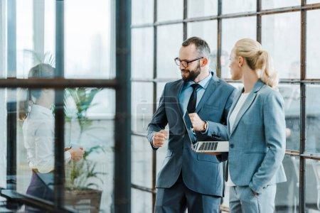 Photo pour Homme d'affaires barbu joyeux regardant collègue tout en se tenant près de femme d'affaires avec ordinateur portable - image libre de droit