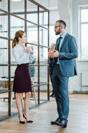 Photo pour Beau barbu homme d'affaires regardant femme d'affaires tenant tasse de café au bureau - image libre de droit