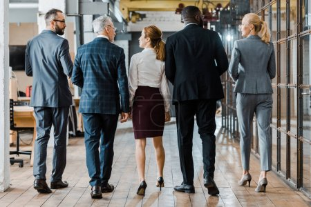 Photo for Back view of multicultural group of businessmen and businesswomen walking in office - Royalty Free Image