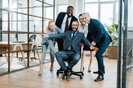 Foto de Cheerful businessman sitting on chair with outstretched hands near multicultural coworkers - Imagen libre de derechos