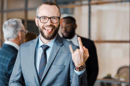 Photo pour Foyer sélectif de l'homme d'affaires heureux affichant la langue et le signe de roche près des collègues multiculturels - image libre de droit