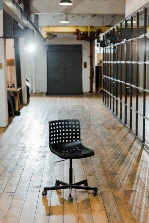 Photo pour Chaise confortable noire sur sol en bois dans un bureau moderne - image libre de droit